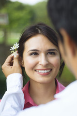 Hispanic husband putting flower behind wife's ear