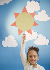 African American girl holding up paper sun