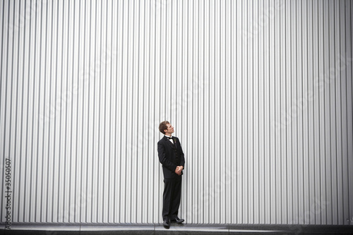 Uncertain groom standing near wall