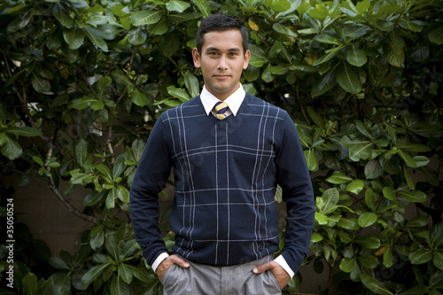 Mixed race businessman standing with hands in pockets