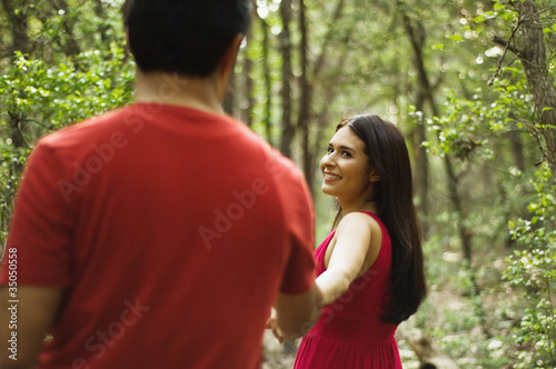 Hispanic couple holding hands and walking outdoors