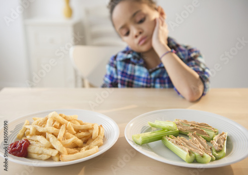 African American girl looking at healthy and unhealthy food