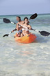 Happy couple paddling kayak in tropical ocean