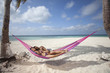 Couple laying on tropical beach in hammock