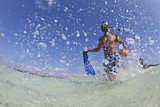 Hispanic man walking in water with snorkel gear