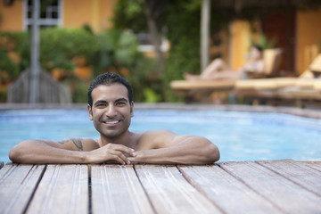 Hispanic man leaning on edge of swimming pool