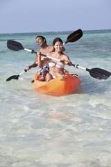 Happy couple paddling kayak in tropical ocean