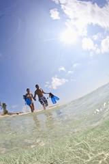 Couple wading in ocean carrying snorkeling gear