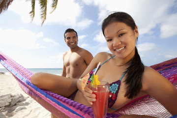 Couple with cocktails enjoying hammock on beach