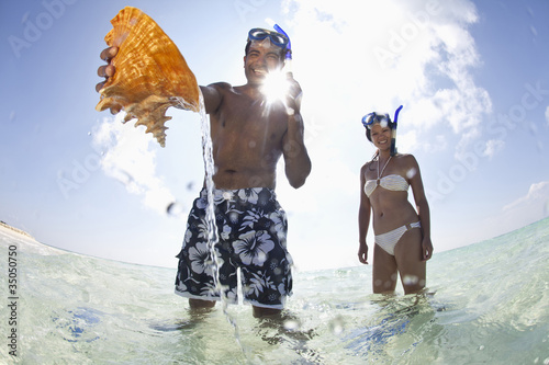 Couple discovering shell in ocean