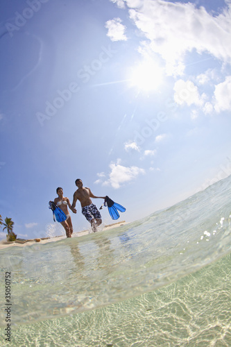 Couple wading in ocean carrying snorkeling gear
