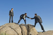 Businessman helping co-worker onto rock