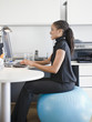 African American woman sitting on exercise ball at desk