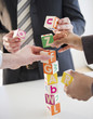 Business people stacking alphabet blocks
