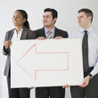 Business people holding whiteboard with arrow