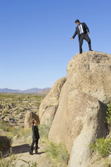 Businesswoman looking at co-worker on top of rock