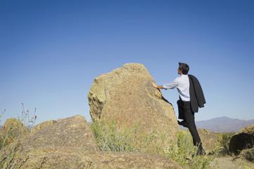 Caucasian businessman standing near rock