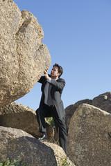Caucasian businessman pushing large rock