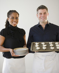 Caterers holding plates and tray of food