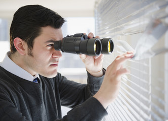 Hispanic businessman peering through window with binoculars