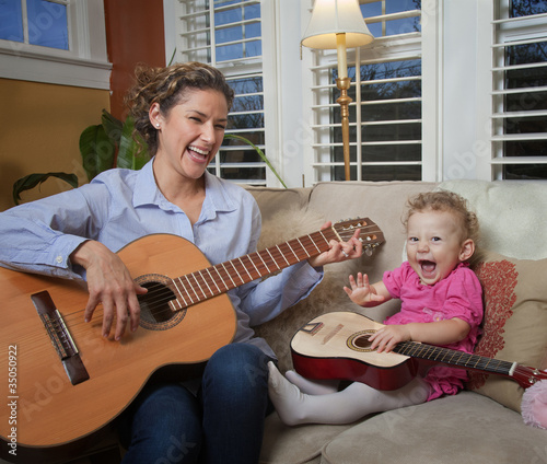 Hispanic mother playing guitar with daughter
