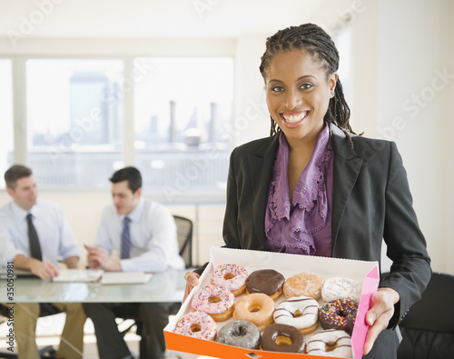 African American businesswoman carrying box of donuts