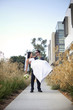Groom carrying bride on sidewalk