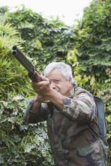 Senior Chilean man pointing shotgun