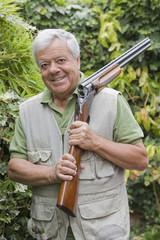 Senior Chilean man holding shotgun