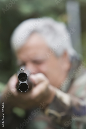 Senior Chilean man pointing shotgun