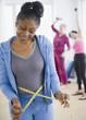 Mixed race woman measuring her waist