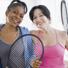 Friends standing together with tennis racquets