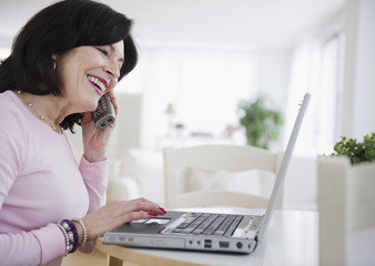 Mixed race woman using laptop and talking on telephone
