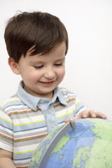 Hispanic boy looking at globe