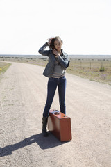 Mixed race woman standing on dirt road with suitcase