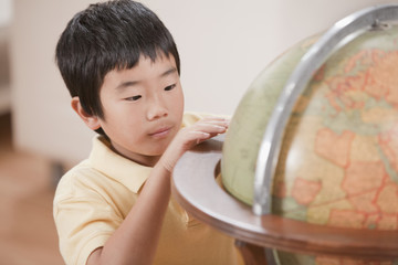 Korean boy looking at globe