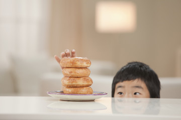 Korean boy taking donut from stack
