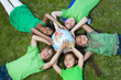 Children laying in grass around globe