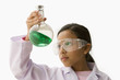 Hispanic girl looking at liquid in beaker