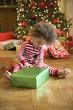 Mixed race boy opening Christmas gift
