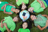 Children laying in grass around globe with solar panel