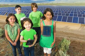 Children standing together in solar panel field
