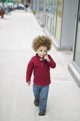 Mixed race boy walking on sidewalk talking on cell phone