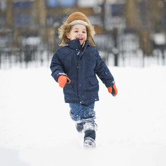 Mixed race boy running in snow