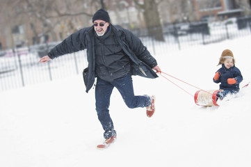 Grandfather pulling grandson on sled in snow