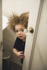 Mixed race boy opening bathroom door