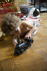 Mixed race boy pushing toy train