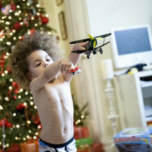 Mixed race boy playing with toy airplanes