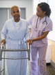 Nurse helping woman use walker in hospital hallway
