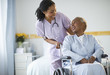 Nurse pushing woman sitting in wheelchair in hospital
